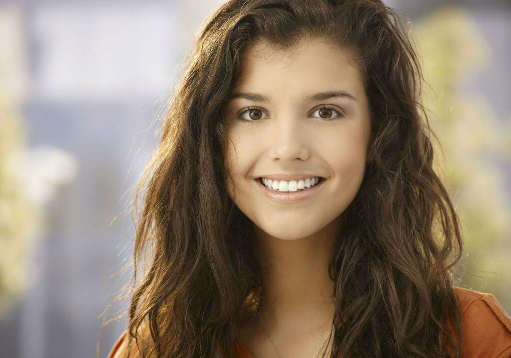photo of a young woman dental implant patient who is smiling at the camera