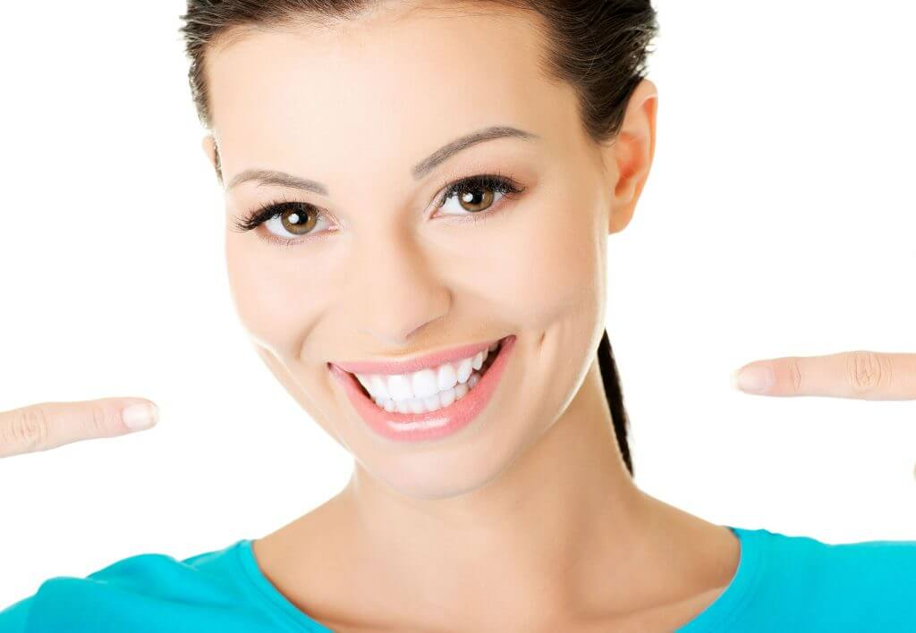 photo of a woman smiling and pointing to her teeth which have been whitened with kor whitening
