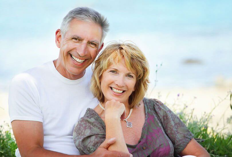 photo of a couple relaxing on the beach and smiling to show their smile makeovers