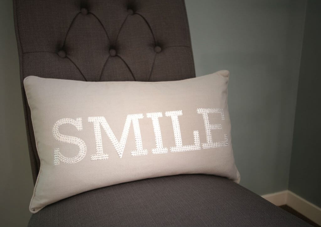 photo of a pillow in Dr. Dennis's office that says smile