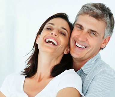 photo of a couple embracing and smiling to show their natural looking dentures