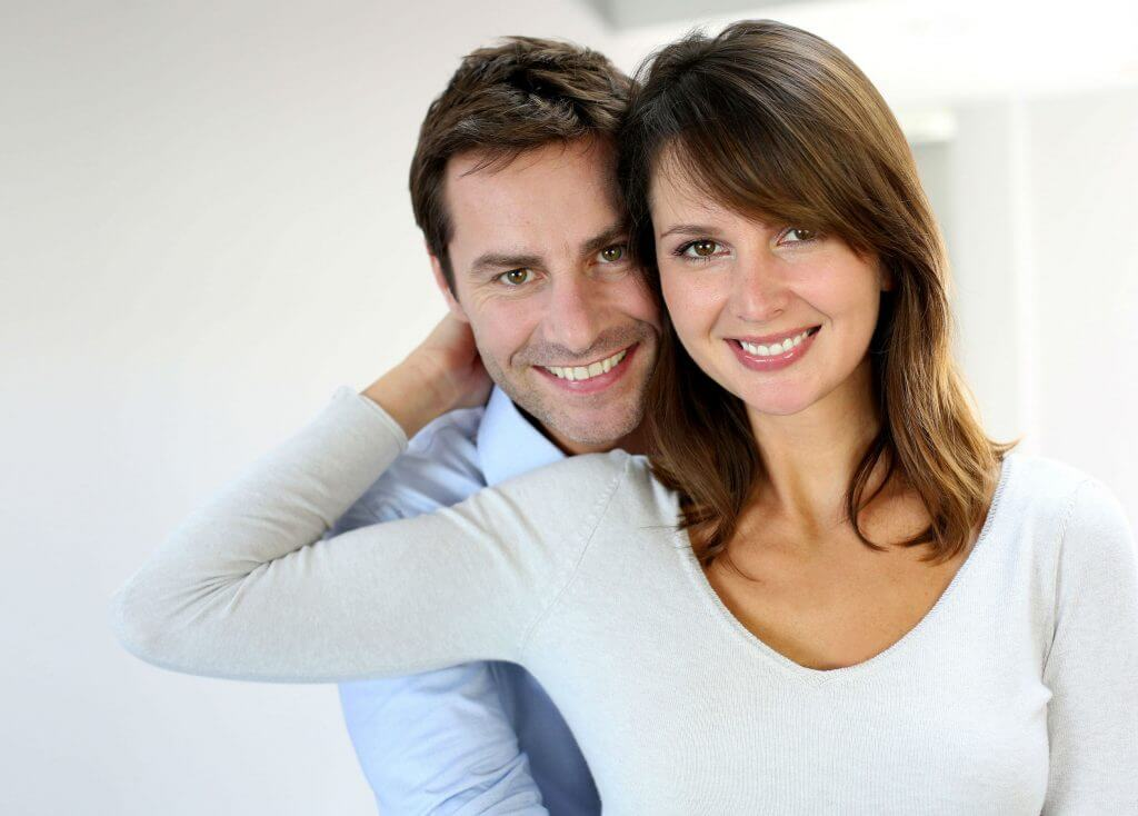 photo of a couple smiling and showing their porcelain crowns