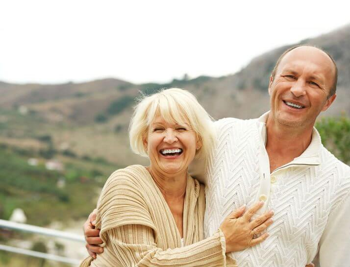 laughing couple near mountains smiling to show their implant overdentures