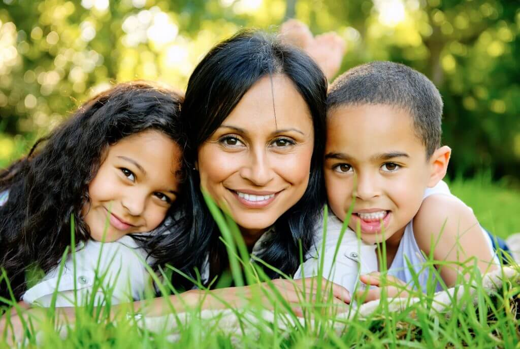 photo of a hispanic mother and her two children lying in the grass and smiling at the camera waiting for pediatric dentist