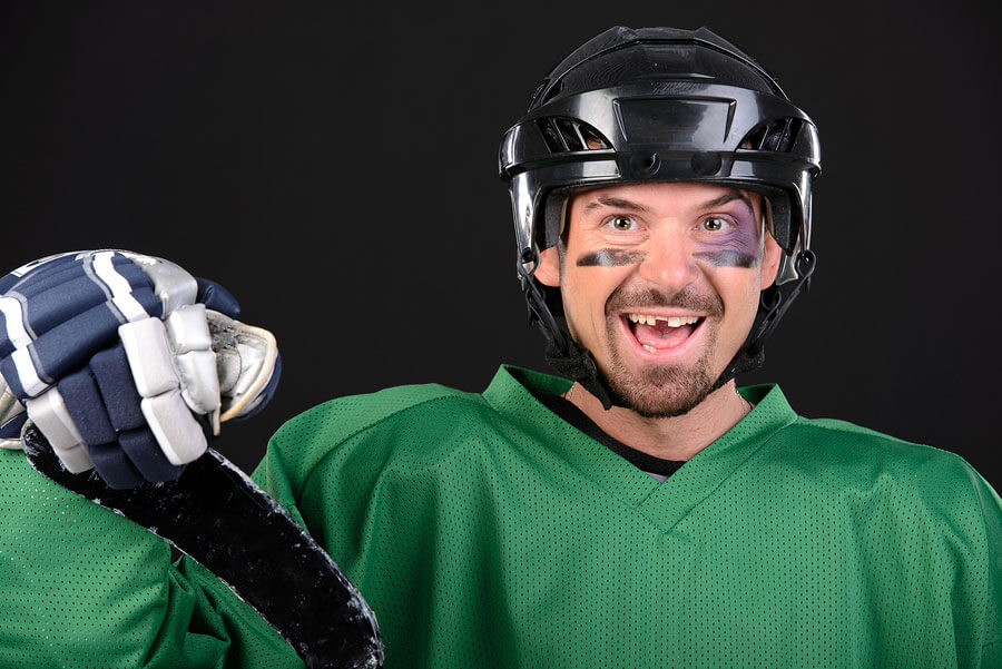 hockey player in uniform with a tooth knocked out