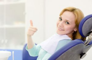 A smiling woman giving a thumbs up from the dental chair