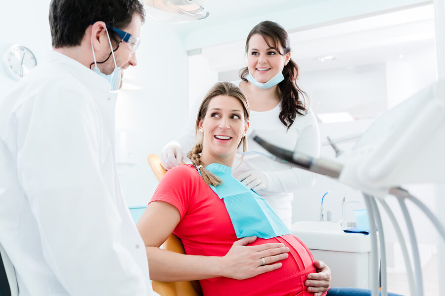 pregnant woman in red dress getting dental care
