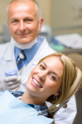 patient smiling in dental chair wtih dentist bheind them