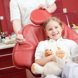 child smiling in a dental chair